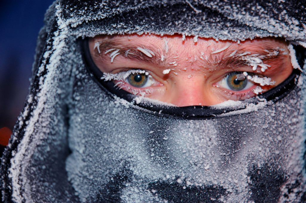 A Man with a covered nose and mouth, with frost on his eyebrows and lashes.